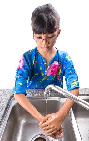 lavarse las manos: Asia malayo niña lavándose las manos jóvenes en el fregadero de la cocina