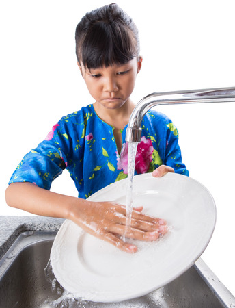 Young Asian Malay girl washing dishes at the kitchen sink photo