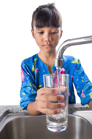 Young Asian Malay girl filling a glass with tap water at the kitchen sink photo
