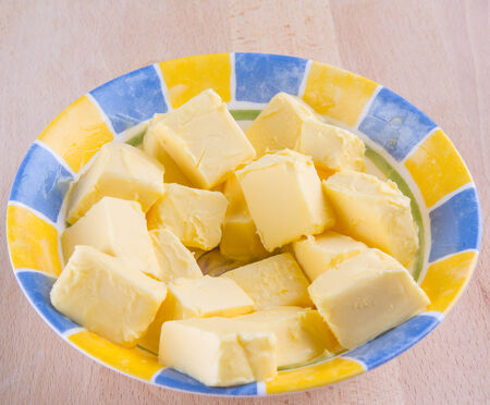 butterfat: A group of melting butter in a bowl on a pastry board Stock Photo