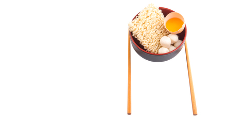 Instant noodle with chicken egg and fish ball in a bowl with a pair of chopsticks over white background photo