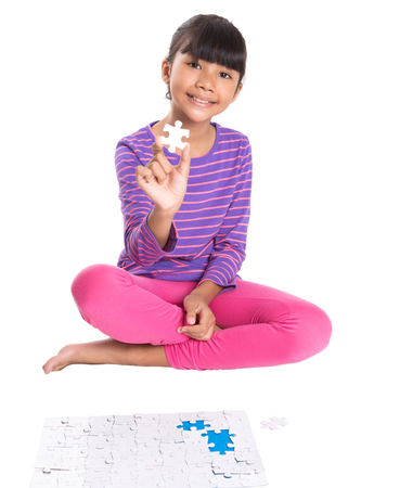 Young Asian Malay girl with jigsaw puzzle pieces over white background photo