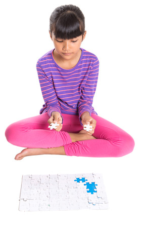 Young Asian Malay girl playing jigsaw puzzle over white background photo