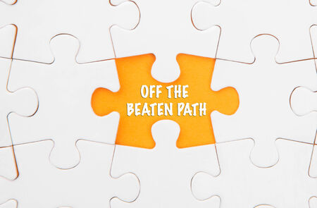 off path: Missing piece of jigsaw puzzle revealing the OFF THE BEATEN PATH words Stock Photo