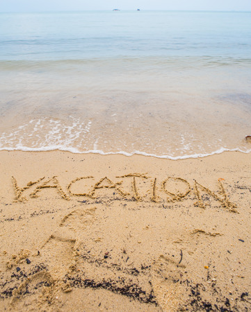 sediments: The VACATION word written on beach sand