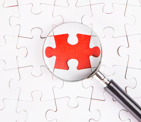 Missing jigsaw puzzle pieces revealing a red surface layer with a magnifying glass Stock Photo