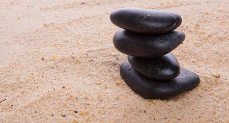 Zen stones buried in beach sand Stock Photo