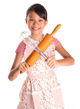Young Asian Malay girl in kitchen apron with egg beater and rolling pin  photo
