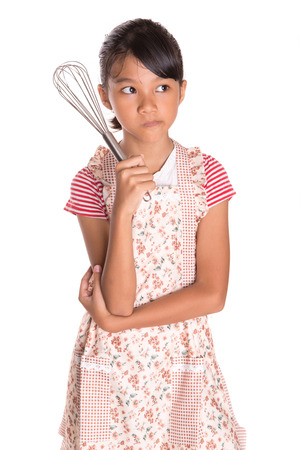 Young Asian Malay girl in kitchen apron holding an egg beater over white  photo
