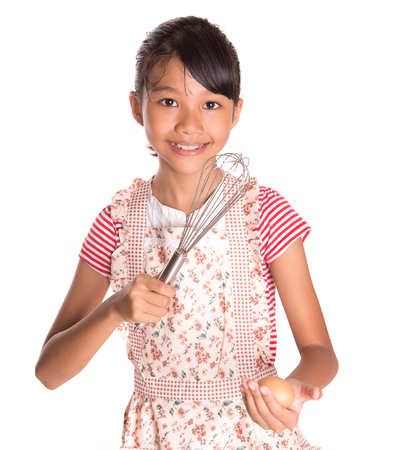Young Malay Asian girl in kitchen apron holding an egg beater with chicken egg over white background photo