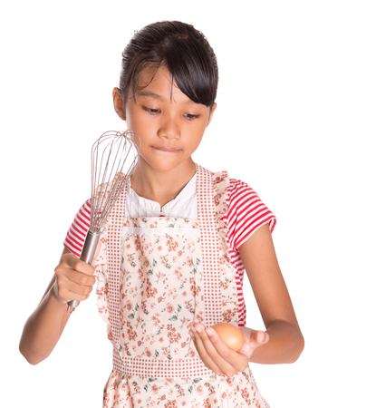 chicken egg: Young Malay Asian girl in kitchen apron holding an egg beater with chicken egg over white background