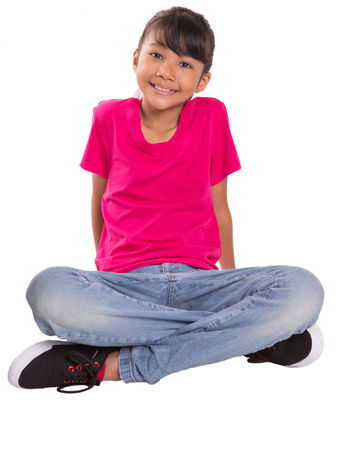Young Malay Asian girl in pink tshirt and blue denim sitting on the floor photo