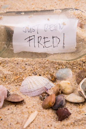 shore line: Concept image of a message JUST BEEN FIRED in a bottle