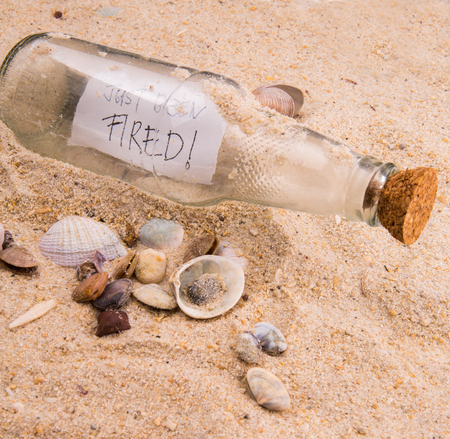 Concept image of a message JUST BEEN FIRED in a bottle photo