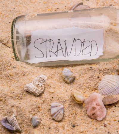 Concept image of a message STRANDED in a bottle photo