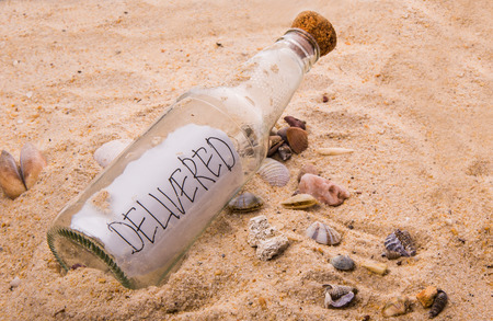 Concept image of a message DELIVERED in a bottle photo