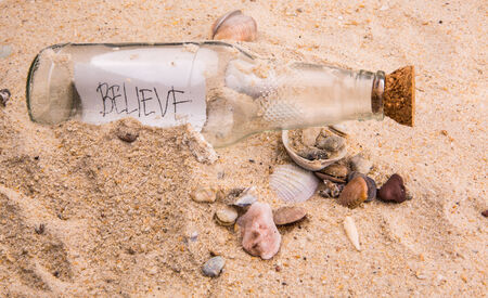 Concept image of a message BELIEVE in a bottle photo