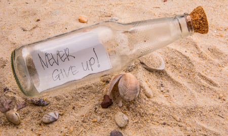 Concept image of a message NEVER GIVE UP in a bottle photo