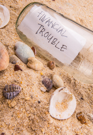 Concept image of a message FINANCIAL TROUBLE in a bottle photo