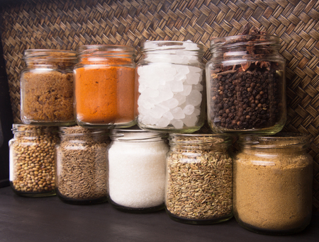 Different varieties of sugar and spices over wicker background photo