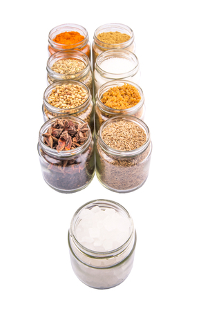 Different varieties of sugar and spices over white background photo