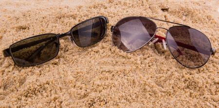 sediments: Pair of sunglasses on beach sand