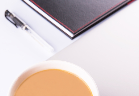 creamer: A mug of coffee with creamer with black notebook and a pen over white background  Stock Photo