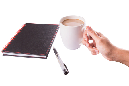 creamer: A woman hand holding a mug of coffee with creamer with a black notebook and a pen