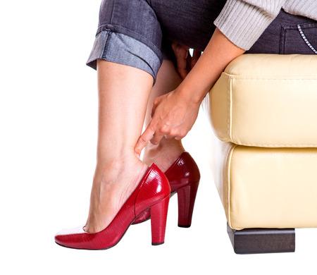 capri pants: Woman rubbing her hurt heel over white
