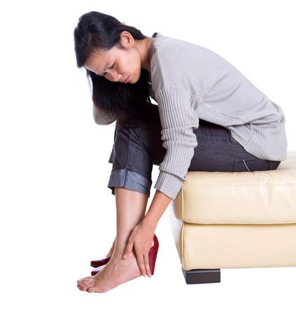 capri pants: Asian female rubbing her hurt heel wearing red heel shoes