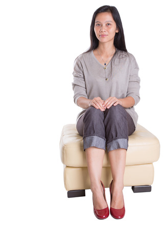 Asian female in casual attire and red heels sitting on couch