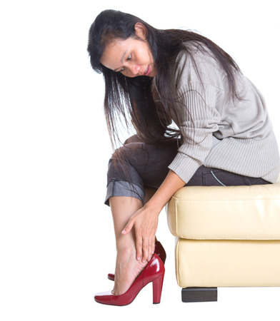 Asian female rubbing her hurt heel wearing red heel shoes photo