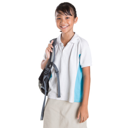 asian preteen: Young Asian school girl with backpack in school uniform over white background Stock Photo
