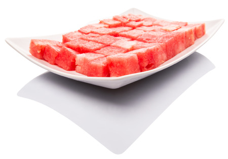 Bite size watermelon on a white plate over white background photo