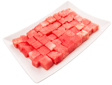 Bite size watermelon on a white plate over white background