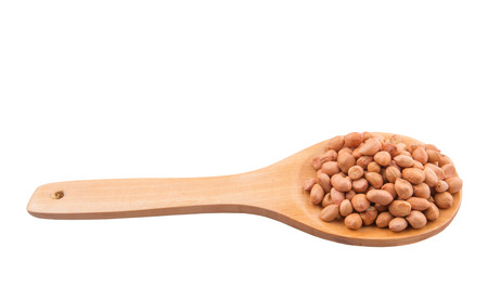 Ground nut or peanut on wooden spoon over white background photo