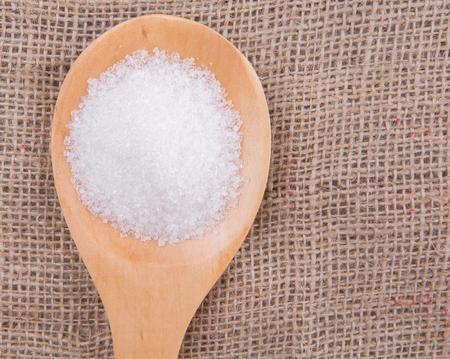 to refine: White refine sugar in wooden spoon on gunny sack background