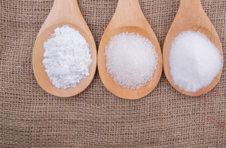 Various type of white sugar in wooden spoon on gunny sack