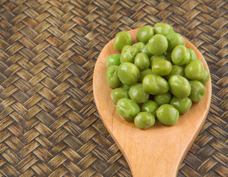 cooking ware: Green  peas on wooden spoon over wicker background