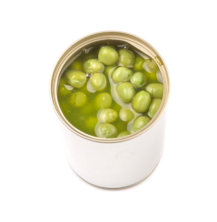 Green peas in a tin can over white background