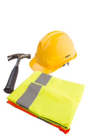 Yellow hard hat, a hammer and orange and yellow reflective vest over white background  photo
