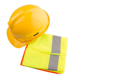 Yellow hard hat and orange and yellow reflective vest over white background photo