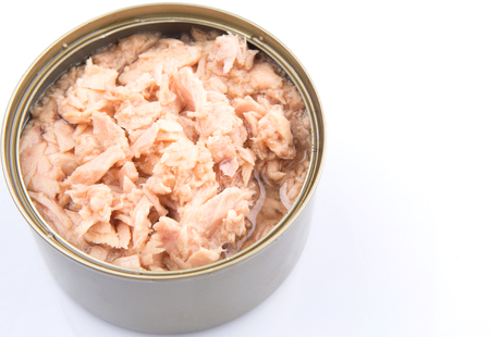 Pieces of tuna fish in a tin can over white background photo