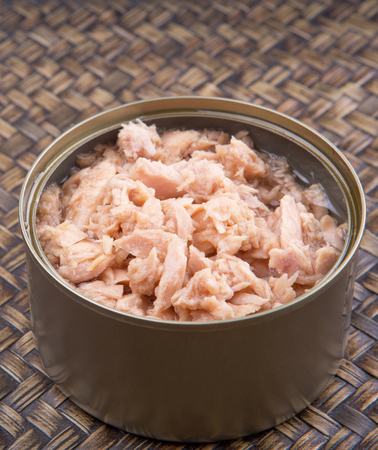 Pieces of tuna fish in a can over wicker background photo