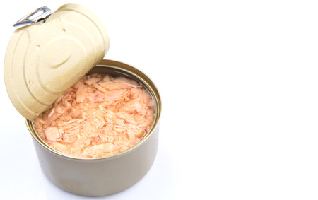 Pieces of tuna fish in a tin can over white background
