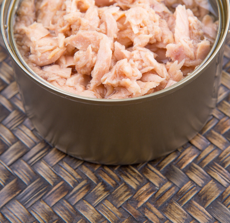 Pieces of canned tuna in a white bowl with a fork on wicker background Stock Photo