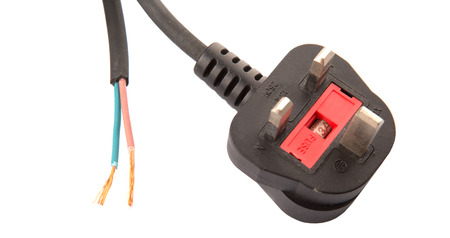 British Standard three pin AC power plugs and exposed electrical wire over white background photo