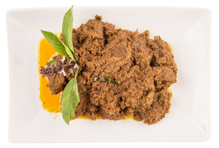 The Beef Rendang, a popular traditional Malay dish on white plate over white