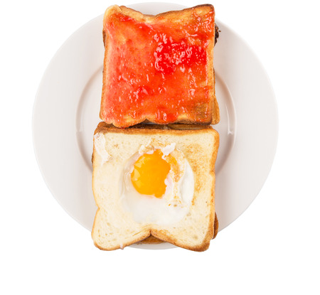 burnt toast: Bread toast with fried egg and strawberry jam on white plate
