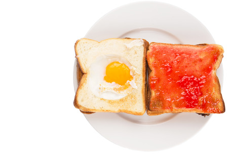 Bread toast with fried egg and strawberry jam on white plate photo